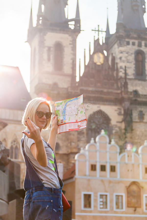 Beautiful young girl in Prague looks at the city map. PRAGUE, CZECH REPUBLIC - JUNE 05, 2016: Woman looks at map in the old town square. Travel guide, tourism royalty free stock image