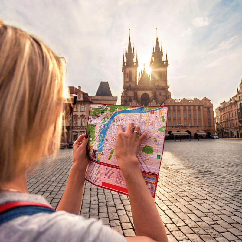 Beautiful young girl in Prague looks at the city map. PRAGUE, CZECH REPUBLIC - JUNE 05, 2016: Woman looks at map in the old town square. Travel guide, tourism stock images