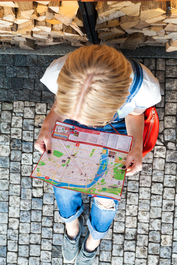 Beautiful young girl in Prague looks at the city map. Top view. PRAGUE, CZECH REPUBLIC - JUNE 05, 2016: Woman looks at map in the old town square. Tourism in royalty free stock photo