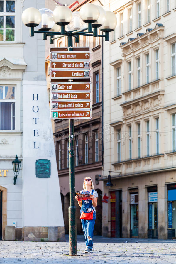 Beautiful young girl in Prague looks at the city map. Woman looks at map in the old town square. Travel guide, tourism in Europe, female tourist with map royalty free stock image