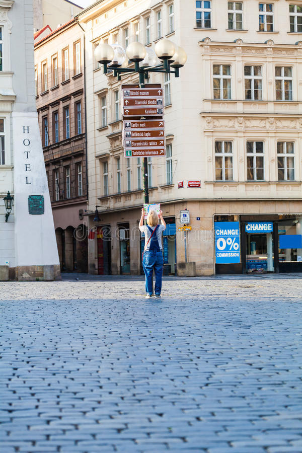 Beautiful young girl in Prague looks at the city map. Woman looks at map in the old town square. Travel guide, tourism in Europe, female tourist with map stock photography