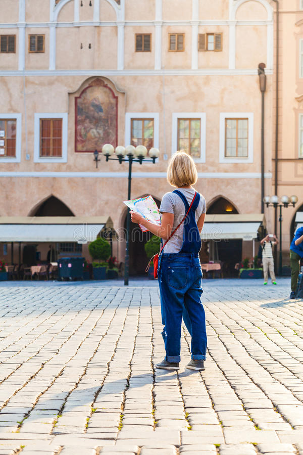 Beautiful young girl in Prague looks at the city map. Woman looks at map in the old town square. Travel guide, tourism in Europe, female tourist with map stock images