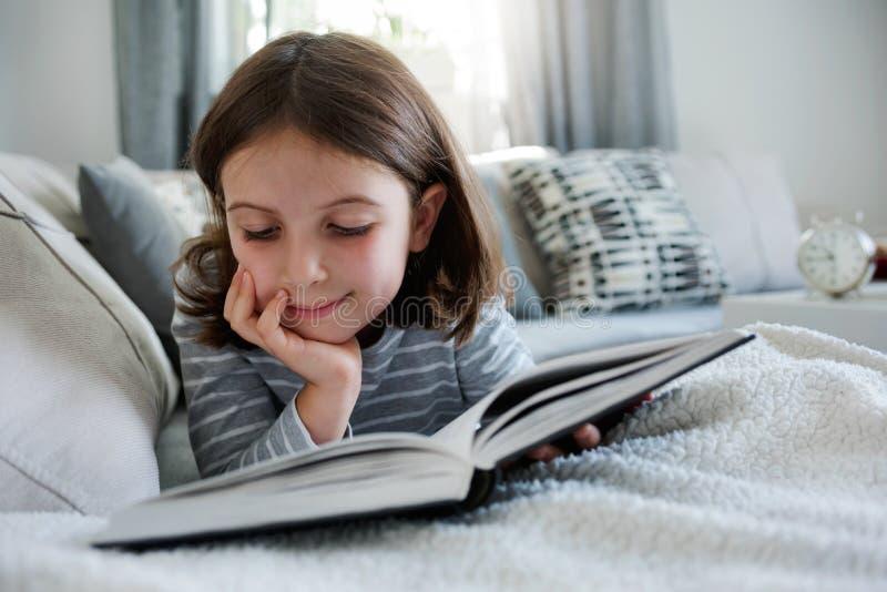 Cute young girl reading book at home stock photos