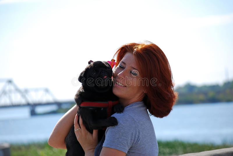 The beautiful young girl with red hair embraces on the street of the pet a black dog of breed a pug. royalty free stock photos