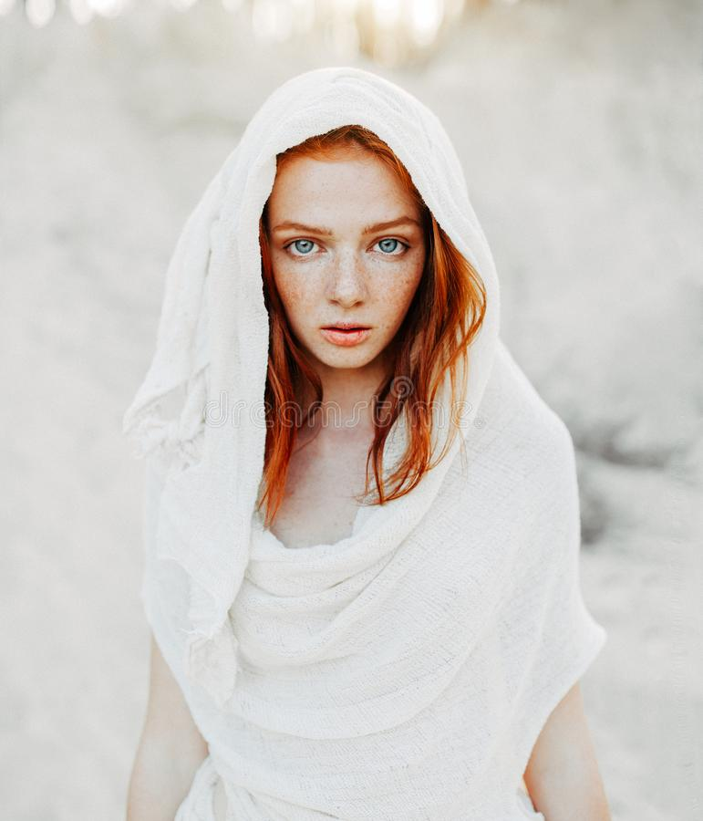 A beautiful young girl with red hair and freckles looks intently at the camera. Woman in the hood and clothes for the desert. stock photography