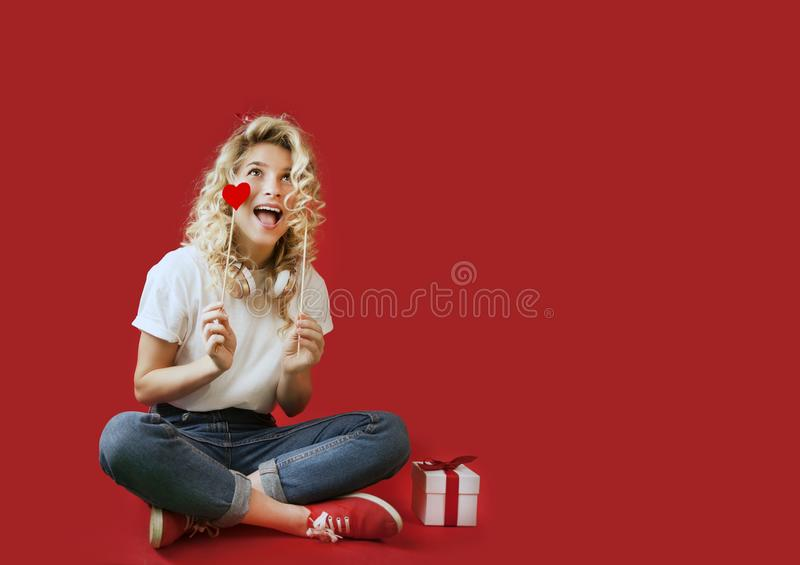 Beautiful young girl with red hearts and a white gift with a bow sits in full growth on an isolated red backgroundValentine`s Day royalty free stock images