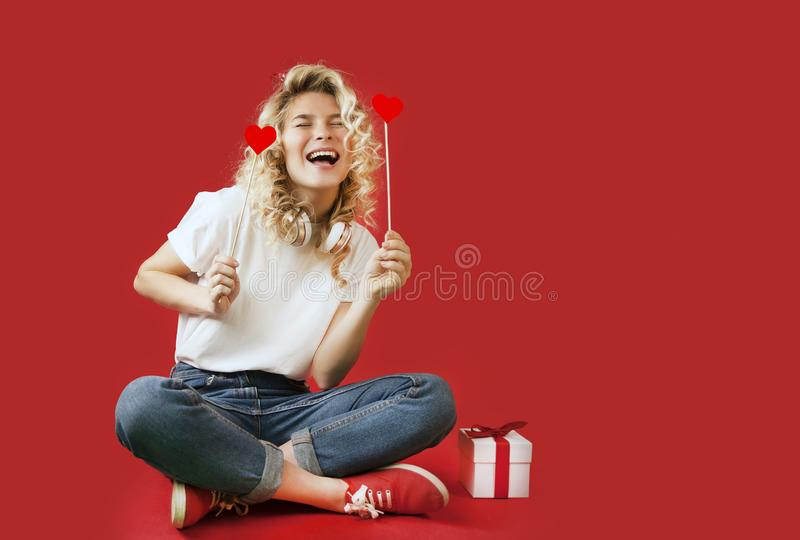 Beautiful young girl with red hearts and a white gift with a bow sits in full growth on an isolated red backgroundValentine`s Day stock photos
