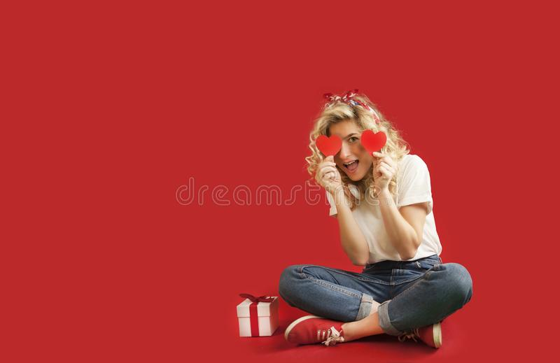 Beautiful young girl with red hearts and a white gift with a bow sits in full growth on an isolated red backgroundValentine`s Day royalty free stock photo