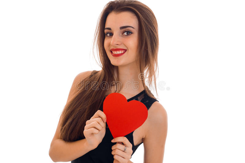 Beautiful young girl with red lipstick is holding a card in the shape of a heart and smiling royalty free stock image