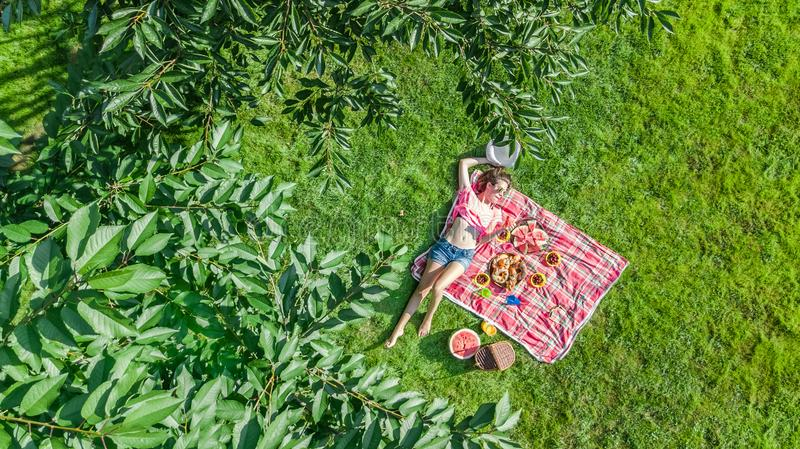 Beautiful young girl relaxing on grass, having summer picnic in park outdoors, aerial view from above. Beautiful young girl relaxing on grass, having summer royalty free stock image