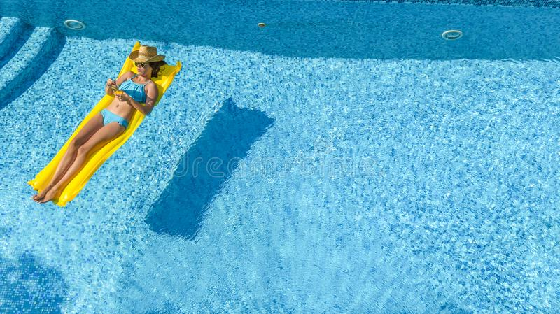 Beautiful young girl relaxing in swimming pool, swims on inflatable mattress and has fun in water on family vacation, aerial view royalty free stock photo