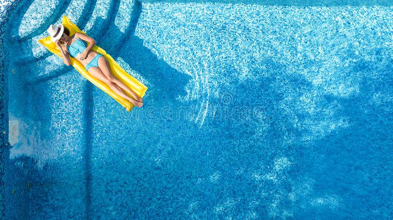 Beautiful young girl relaxing in swimming pool, swims on inflatable mattress and has fun in water on family vacation, aerial view royalty free stock photography
