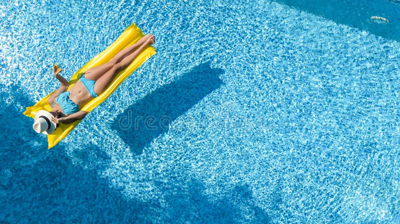 Beautiful young girl relaxing in swimming pool, swims on inflatable mattress and has fun in water on family vacation royalty free stock images