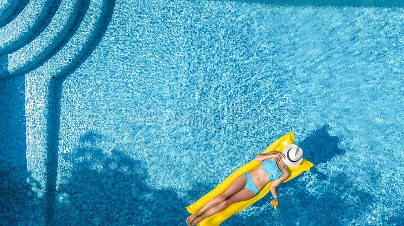 Beautiful young girl relaxing in swimming pool, swims on inflatable mattress and has fun in water on family vacation royalty free stock photo