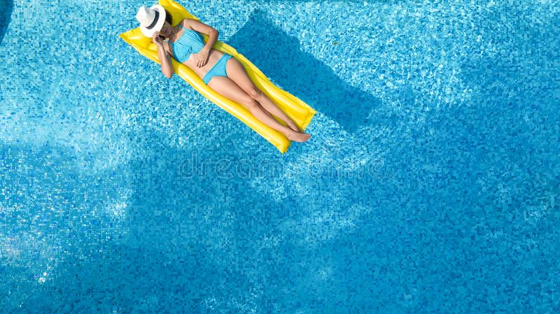 Beautiful young girl relaxing in swimming pool, swims on inflatable mattress and has fun in water on family vacation stock photo