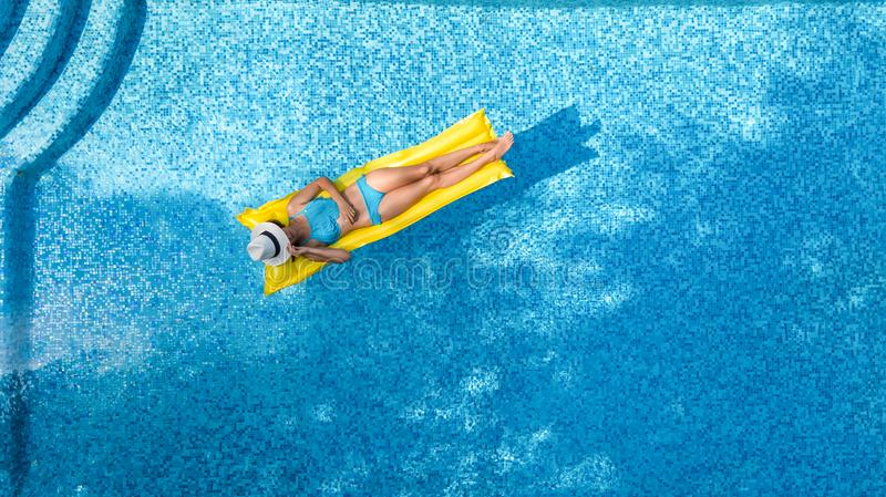Beautiful young girl relaxing in swimming pool, swims on inflatable mattress and has fun in water on family vacation, aerial view stock photos