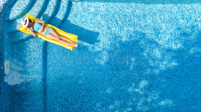 Beautiful young girl relaxing in swimming pool, swims on inflatable mattress and has fun in water on family vacation royalty free stock photos