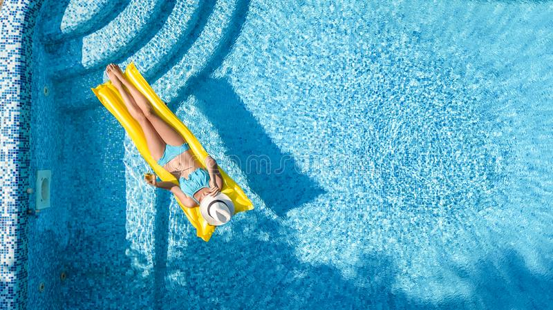 Beautiful young girl relaxing in swimming pool, swims on inflatable mattress and has fun in water on family vacation royalty free stock photography