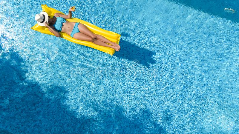Beautiful young girl relaxing in swimming pool, swims on inflatable mattress and has fun in water on family vacation stock images