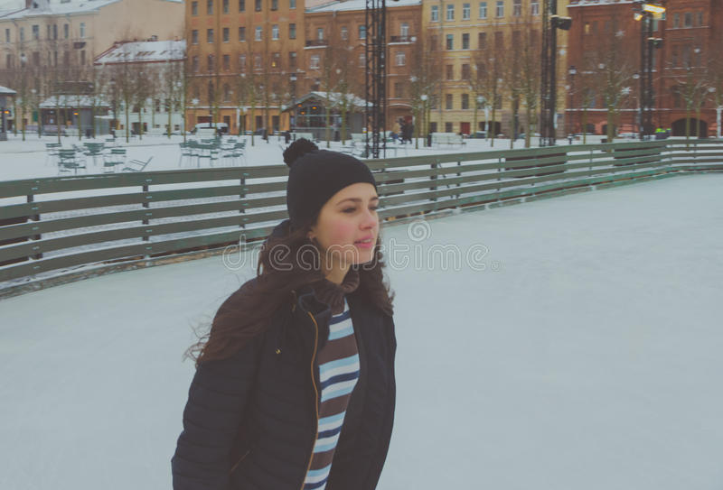 Beautiful young girl at the rink in winter, ice. Beautiful girl at the rink winter, skates royalty free stock photography
