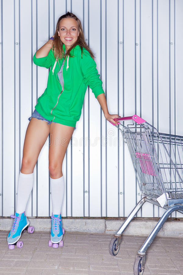 A Beautiful Young Girl In Roller Skates Near Supermarket Trolley Royalty Free Stock Image