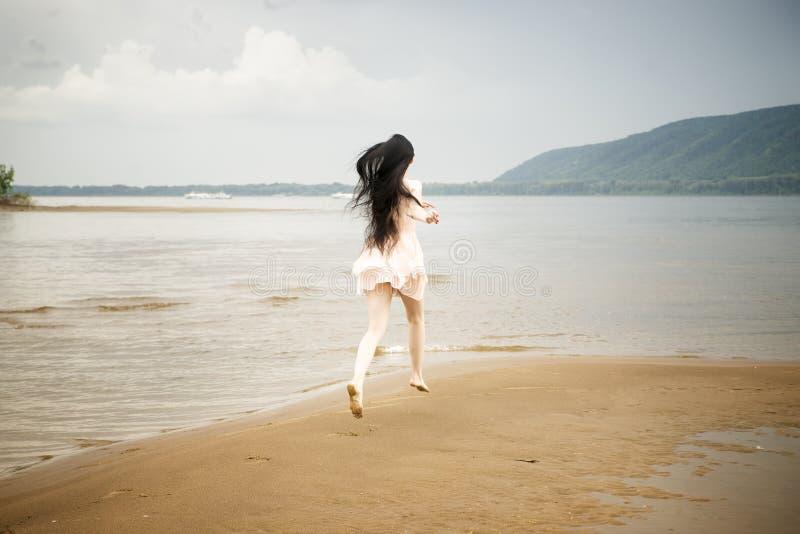 Beautiful young girl runs along the beach stock photo