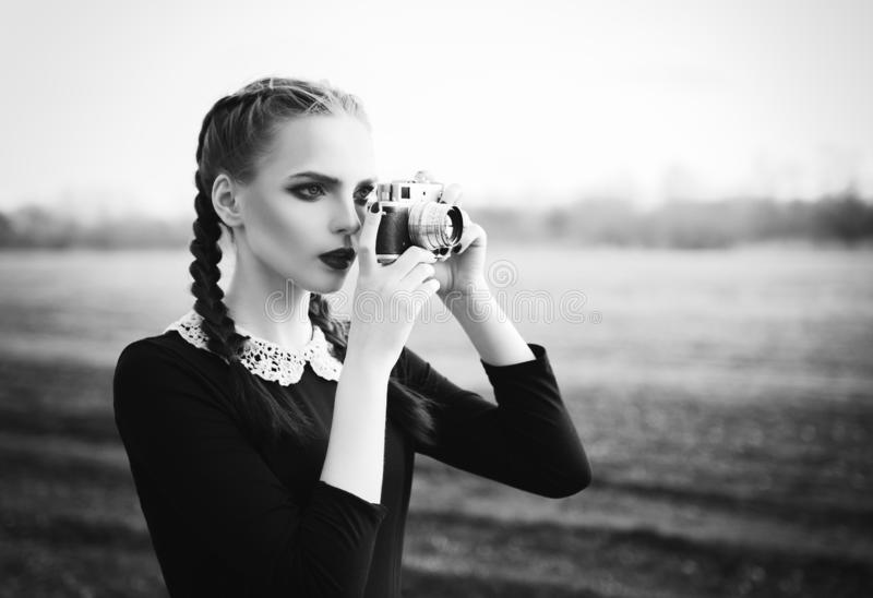 Beautiful young girl shooting by old classic film camera. Outdoor portrait, black and white stock photography