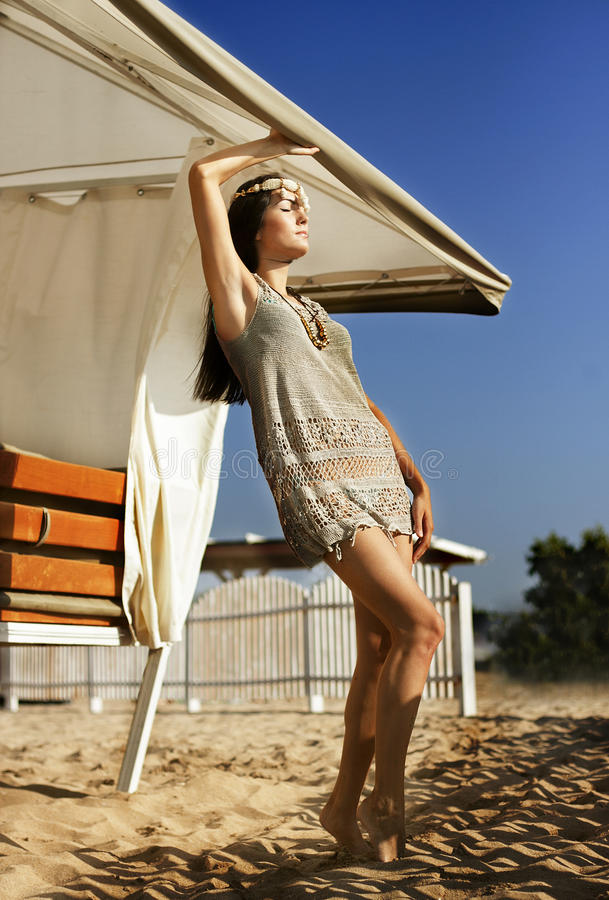 Beautiful young girl short dress standing on sand under an umbrella royalty free stock photo