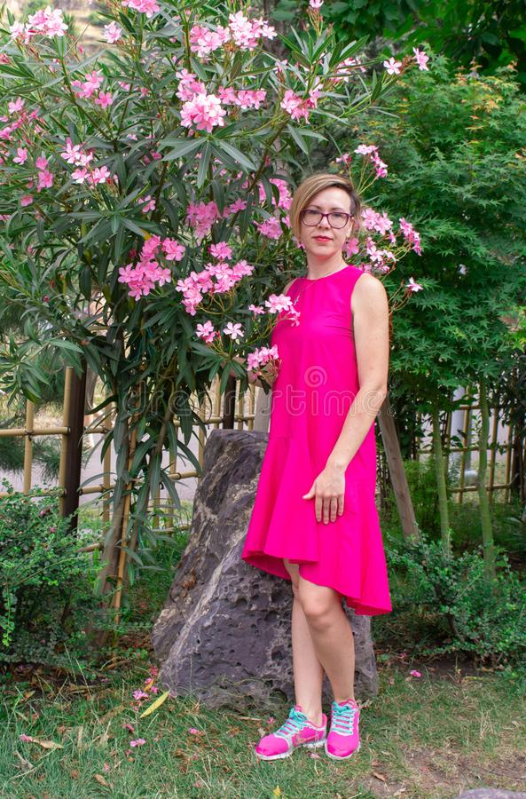 A beautiful young girl, with a short haircut, wearing glasses and a pink dress, walks in a park with flowers on nature. royalty free stock image