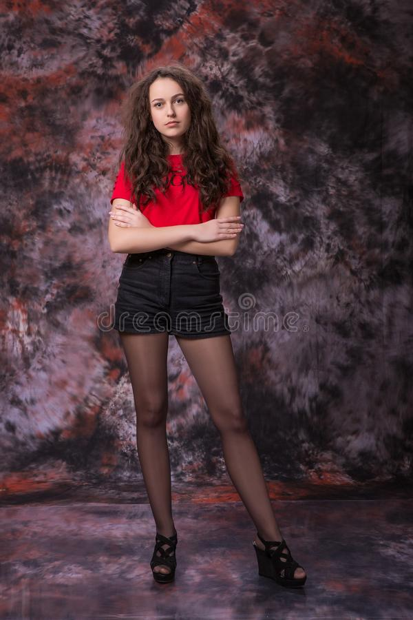 Beautiful young girl in shorts and t-shirt standing on over marble colored background. Fashion photo. Model test stock images