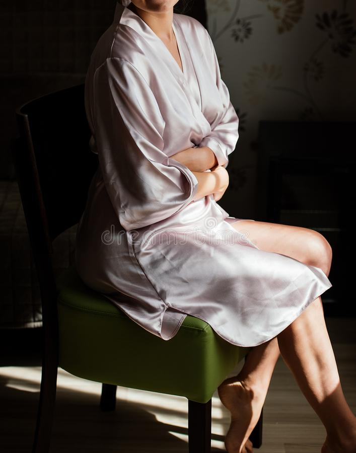 Beautiful young girl in silk robe sitting on chair and crosses. royalty free stock photo