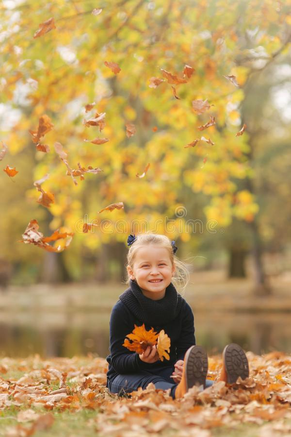 Beautiful young girl sist in leaves and throws them up. Colorful background. Happy little girl smile and have fun stock photo
