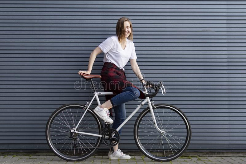 Beautiful young girl sit down on a white bicycle on the background of a gray striped wall, the woman is happy stock image