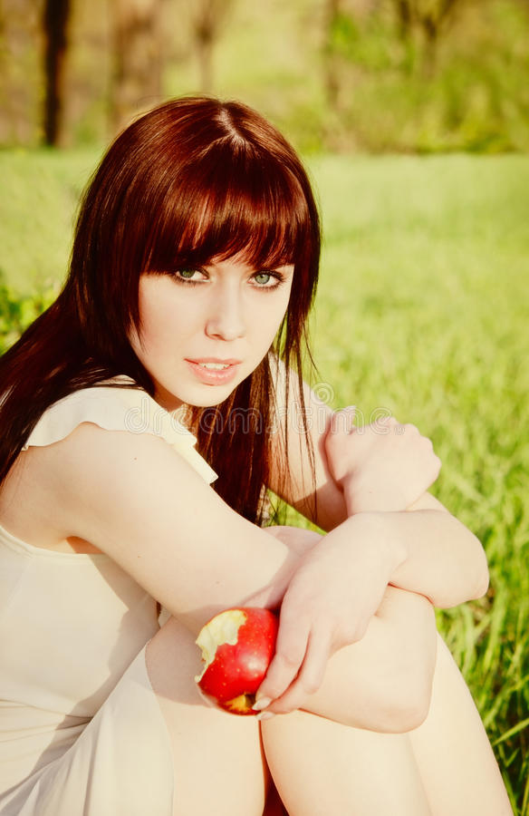 Beautiful young girl sitting with apple in hand stock photo