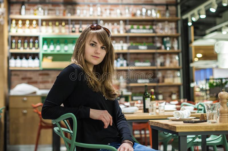 Beautiful young girl sitting in a bar. woman waiting for an aperitif royalty free stock images