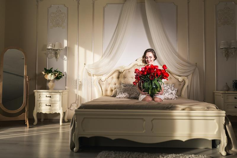 A beautiful young girl is sitting on the bed and holding a lot of red tulips in a vase. March 8 concept. stock images