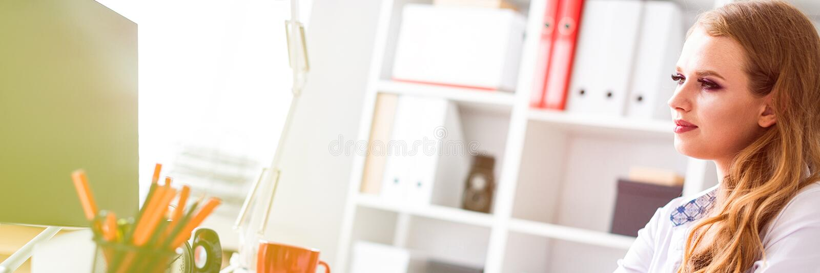 Beautiful young girl sitting at desk in office and working at computer. Before the girl there are documents. stock photos