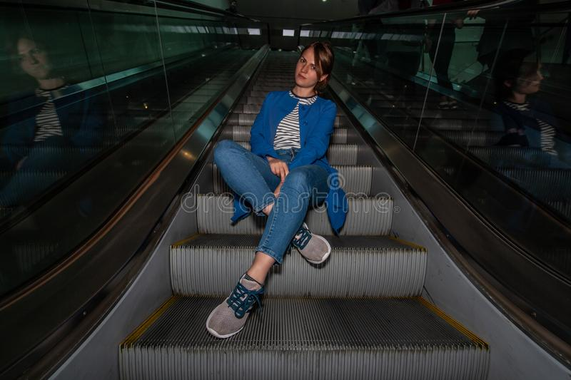 Beautiful young girl sitting on escalator in casual wear royalty free stock photos