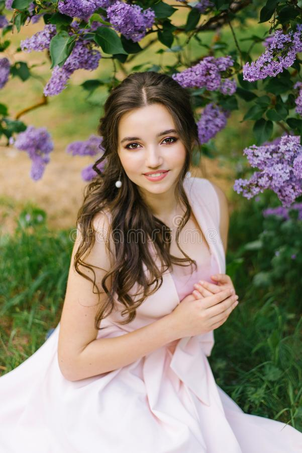 Beautiful young girl sitting on the ground in the garden with blooming lilac. She is happy and smiles a beautiful smile with white teeth. Professional makeup stock image