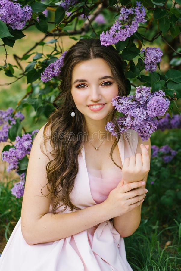 Beautiful young girl sitting on the ground in the garden with blooming lilac. She is happy and smiles a beautiful smile with white. Teeth. Professional makeup royalty free stock photo