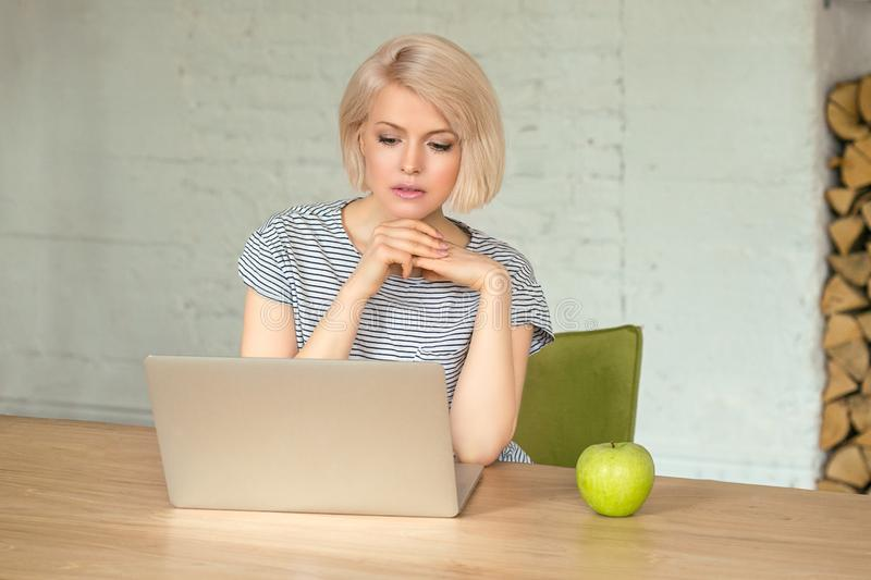 Girl with laptop at home. Beautiful young girl sitting at home and working with laptop, green apple on table royalty free stock photo