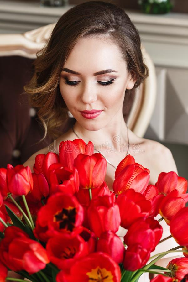 A beautiful young girl is sitting on the sofa and holding a large bouquet of red tulips. March 8 concept. Morning of the bride. stock images