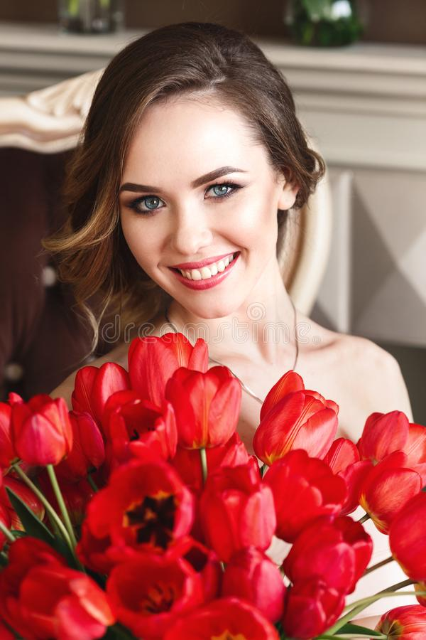 A beautiful young girl is sitting on the sofa and holding a large bouquet of red tulips. March 8 concept. Morning of the bride. stock image