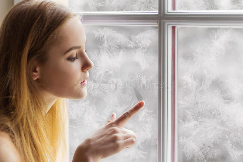Beautiful young girl sitting by the window winter day and draws the sun on the frozen window royalty free stock images