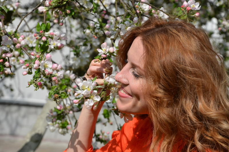 Beautiful young girl smelling a scent of spring flowers stock photo