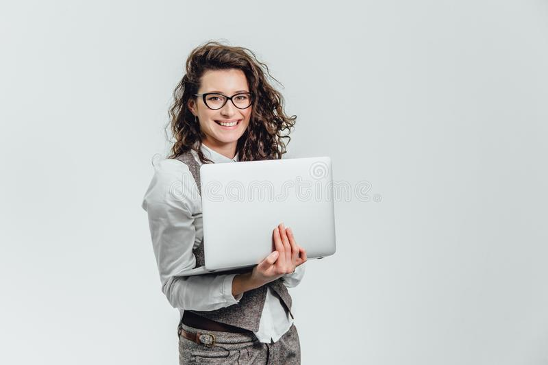 BBeautiful young girl smiles. Works on a laptop in glasses and a white shirt stock photography