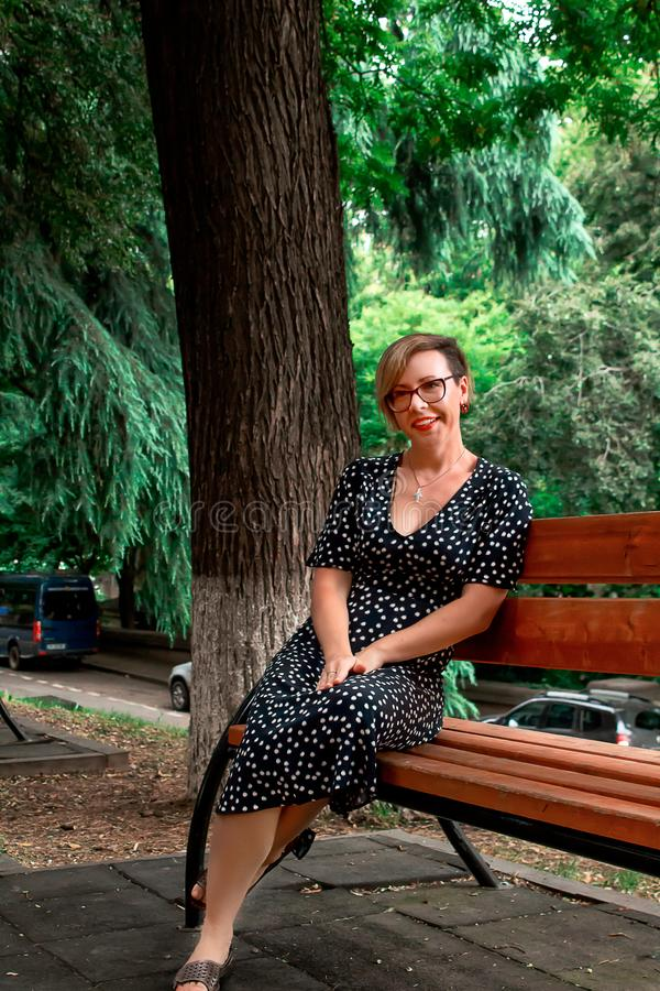 Beautiful young girl smiling, with a short haircut, wearing glasses, sitting on a bench, in nature. royalty free stock image