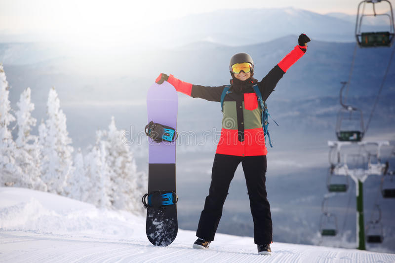 Beautiful young girl with a snowboard. At winter resort stock image
