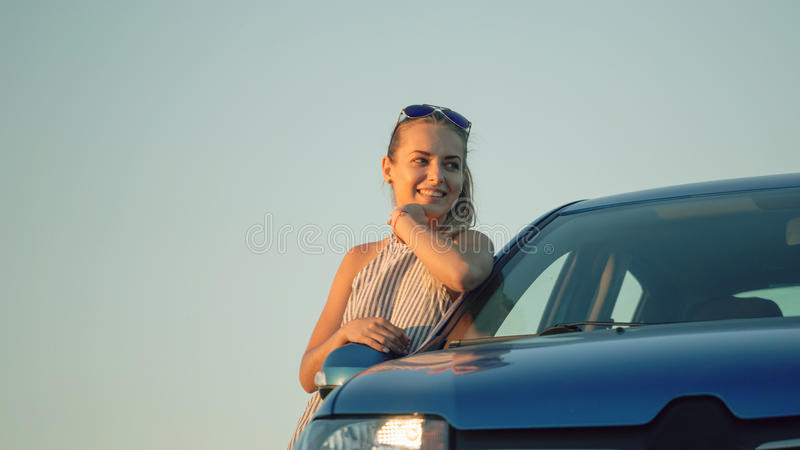 Beautiful young girl standing at the car into the sunset.  royalty free stock photography