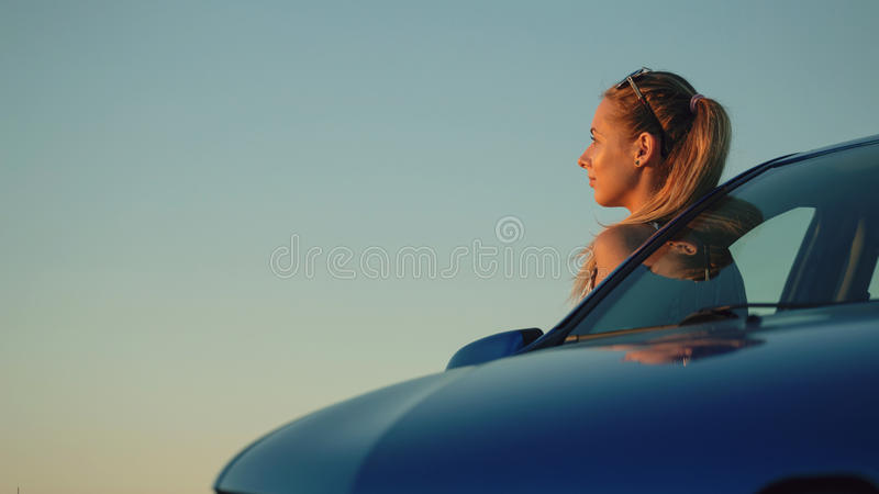 Beautiful young girl standing at the car into the sunset.  royalty free stock images